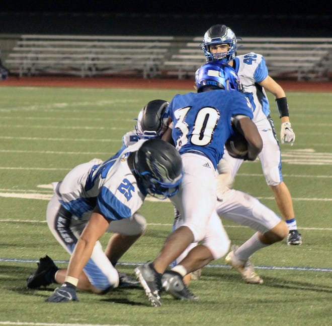 Grain Valley's Hunter Newsom (25) tries to bring down Raytown running back Zahmari Gary (30) in Friday's game at Ted Chittwood Stadium. Gary ran for 255 yards and scored the winning touchown with four seconds left to lift the Blue Jays to a 21-14 victory.