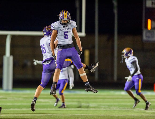 Blue Springs' Carson Willich (5) leaps with teammate Brendan Bledsoe (35) to celebrate as the final seconds tick off the clock in a 28-13 victory over Blue Springs South. It was the seventh straight win for the Wildcats in the Cat Clash series and the 20th in 30 meetings between the crosstown rivalls.