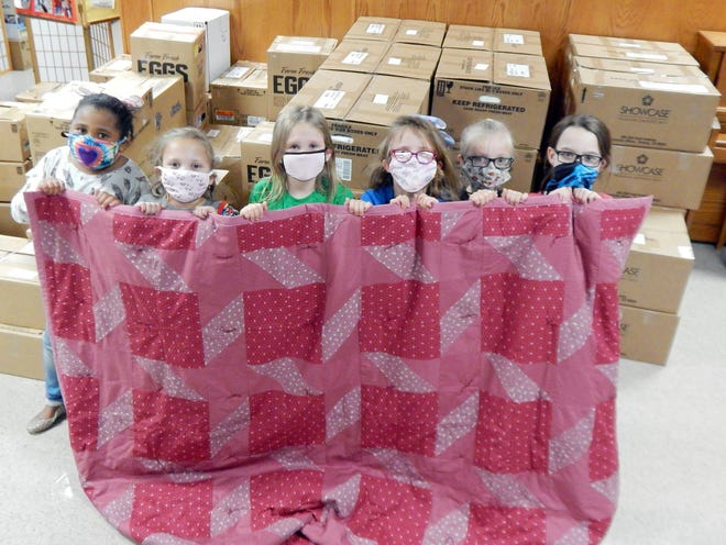 Members of Girl Scout Troop 2825 shown, from left to right, Macarra William, 8; Mia Lowe, 8; Aleah Hill, 7; Emma Kerby, 8; Adley Stevenson, 8; Cheyenne Brown, 9, holding a quilt Friday in Burlington. The quilt will be auctioned later this year to help raise money for Lutheran World Relief. Burlington's Messiah Lutheran pastor Susanne Smith organized volunteers who made over 150 quilts and the hundreds of personal care kits and book bags full of school supplies seen behind the girls.