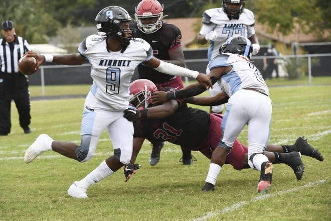 Ribault quarterback Santana Jackson (9) tries to elude the Raines pass rush during the second half of the Northwest Classic. [Stan Badz/Special to The Florida Times-Union]