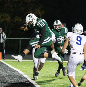 Aurora quarterback Alex Moore leaps into the end zone during the Greenmen's 41-24 home playoff win Oct. 16 vs. Notre Dame-Cathedral Latin.