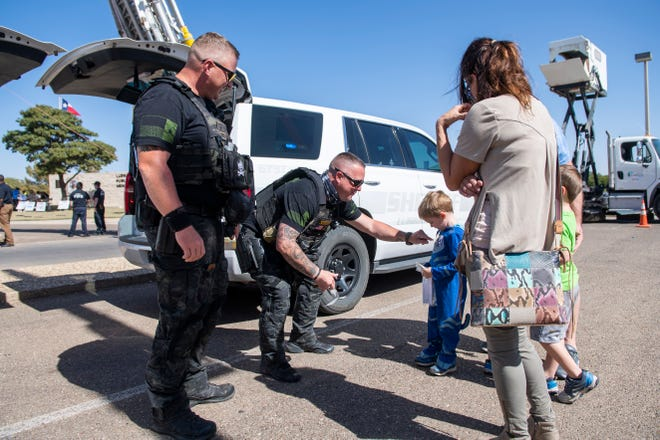 Lubbock County Sheriff Deputy Mike Daniel and Sergeant Josh Bartlett hand out stickers at the 5-5-5 Move Over Slow Down rally on Saturday, Oct. 17, 2020, at Leroy Elmore Park in Lubbock, Texas.