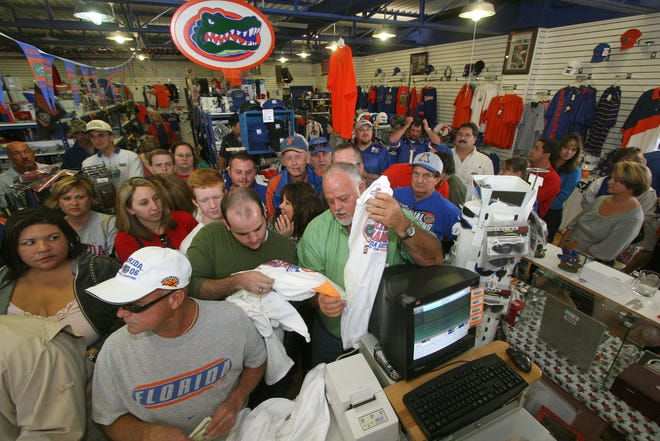"University of Florida fans crowd the Proud Gator store to purchase official ""locker room"" shirts depicting the Gators as 2006 BCS Bowl National Champions at the shop on South Florida Avenue in Lakeland. These are the shirts which were handed out to the team on the field after they defeated Ohio State. Chuck Carper, owner of Proud Gator, said he received multiple shipments of approximately 2,500 shirts. MICHAEL WILSON/LEDGER CORRESPONDENT"