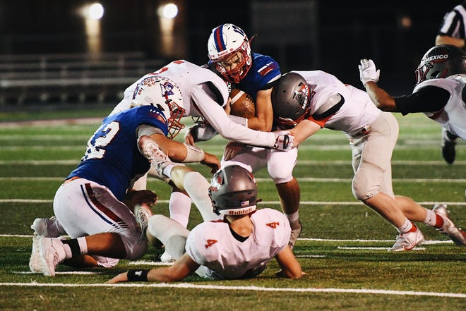 Moberly senior Dominic Stoneking (12) holds onto the ball during a North Central Missouri Conference game against Mexico on Friday night at Moberly High School.