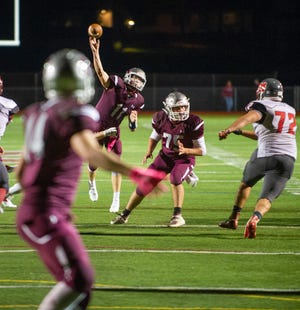 Newton quarterback Jack Young (11) unloads a touchdown pass to receiver Dylan Bailey, front, during the teams' game on Oct. 16 at Newton High School. [Photo by Warren Westura/For the New Jersey Herald]
