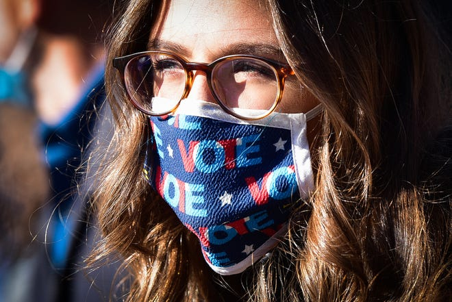 """New Hartford resident Justine Bartnick wears a """"VOTE"""" mask while participating in a """"We Will Vote"""" women's march on Saturday, Oct. 17, 2020 in Utica."""