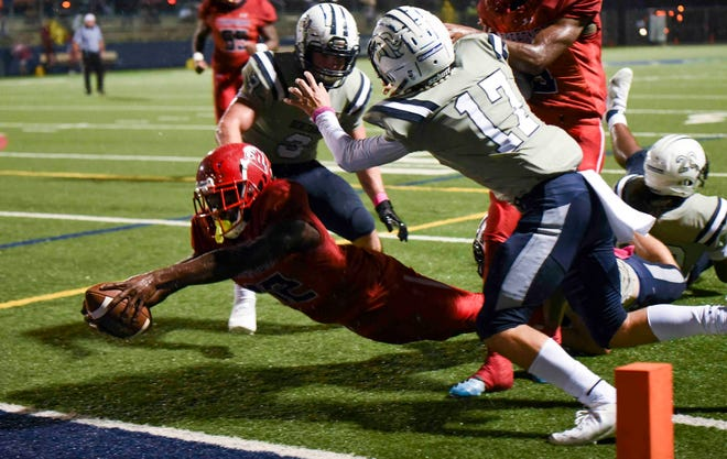 Champagnat Catholic wide receiver Benson Prosper (12) dives for a touchdown past American Heritage defenders Kyle Boone (3) and Jett Coolman (17) for the game's first score Friday. Champagnat Catholic went on to win 33-27 in Delray Beach.