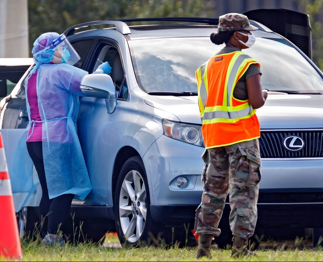 A patient is tested in August for the coronavirus at a drive-up testing center at the FitTeam Ballpark of the Palm Beaches. The Health Care District of Palm Beach County, which operates the site, has overseen 86,000 tests at six locations since March.