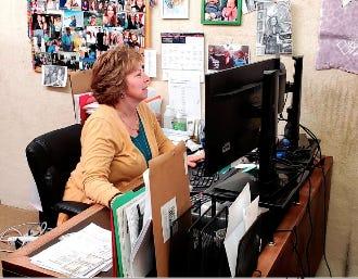 Della Hampton peruses a customer's portfolio at her accounting office on S. Main Street in Pratt.