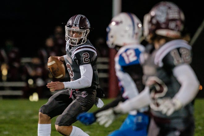 Woodridge quarterback Ben Kiser rolls out for a gain in yardage against Ravenna during the first quarter Friday, October 16, 2020 in Peninsula.