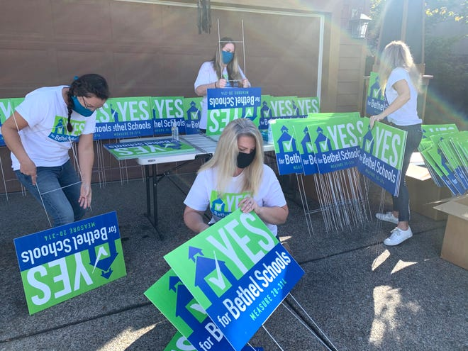 Kristen Dufek (front center), chair of the Friends of Bethel Schools campaign committee, puts together signs with other volunteers to distribute in support of the 2020 Bethel School District bond.