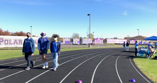 Jackson High School seniors Zachary Charlick (left), Zachary Discenza (center) and Daniel Lee take part Saturday morning in Jackson Township in Walking in Blue, a one-mile walk on their school's track against human trafficking.