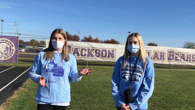 Jackson High School seniors Makenzie Morgan, 17, left, and Aly Stanislawski, 18, talk Saturday morning at Jackson High School in Jackson Township about organizing Walking in Blue, a one-mile walk and fundraiser to combat human trafficking. Setting up the event was part of their senior project as students in the Jackson Academy for Global Studies.