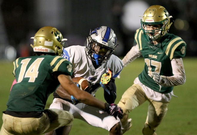 Bartram Trail running back Eric Weatherly, center, runs between Nease defensive backs Jordan Wilhite, left, and Creed McClafferty on Oct. 16, 2020.