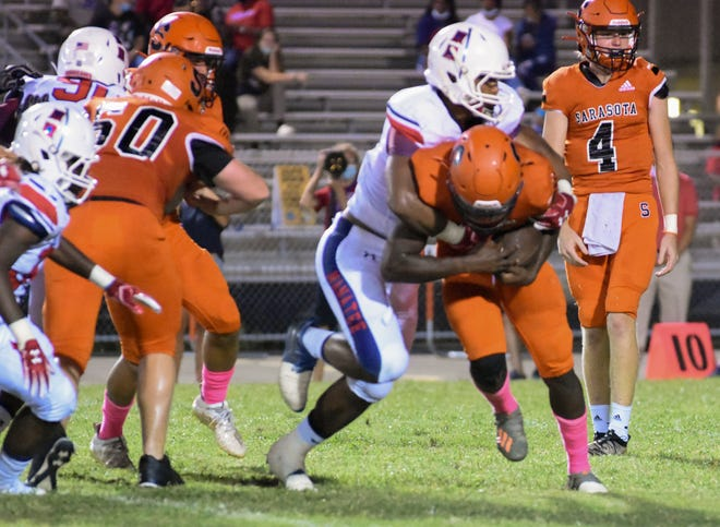 A Sarasota player gets taken down by the Manatee High defense at Ihrig Field in Sarasota on Friday. The Hurricanes defeated the Sailors, 36-13