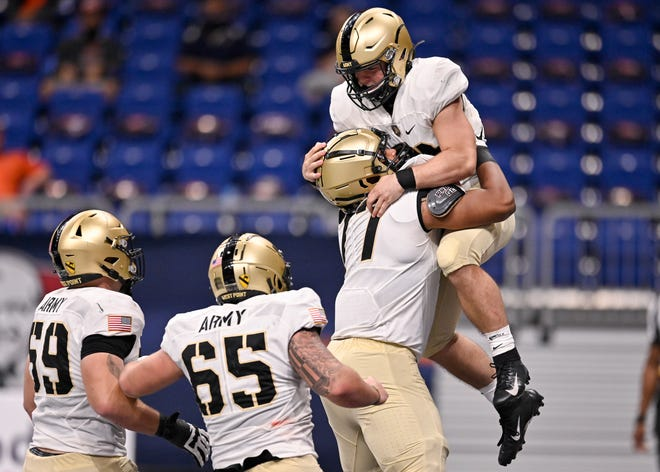 Army freshman quarterback Cade Ballard, right, celebrates his first career touchdown with teammates Jordyn Law, Noah Knapp (65) and Mike Johnson (59) during a 28-16 win over UTSA. Ballard helped Army to its first 5-1 record since 1996 in his first college start. DARREN ABATE/AP