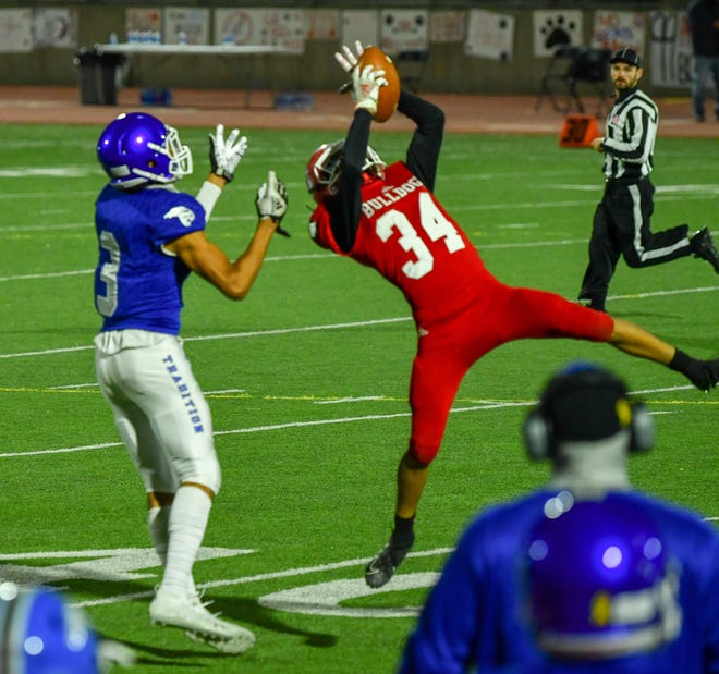 Pueblo Centennial's Marcus Abeyta, right, comes up with an interception in the third quarter of the 72nd annual Bell Game on Friday, Oct. 16, 2020, at Dutch Clark Stadium.