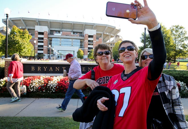 Despite two home football games in the past 30 days that brought fans like Cheryl Coker, Donna Ertzberger and Jamie Savage, seen here take a selfie with Bryant-Denny Stadium on Saturday, local efforts have helped slow the spread of COVID-19 infections in the Tuscaloosa area, Mayor Walt Maddox said. [Staff file photo/Gary Cosby Jr.]