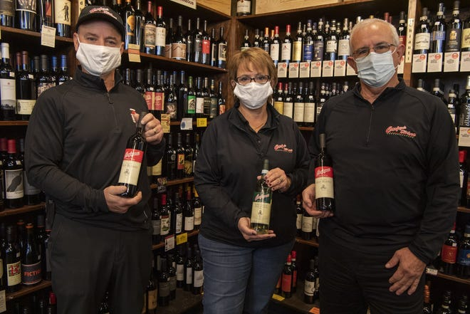 Siblings Sam Carfagna (left), Julie Riley and Dino Carfagna hold bottles of Carfagna's branded wine Oct. 16 in the wine section of Carfagna's Market in Northland. They are moving the market to 1440 Gemini Place, near Polaris Fashion Place.