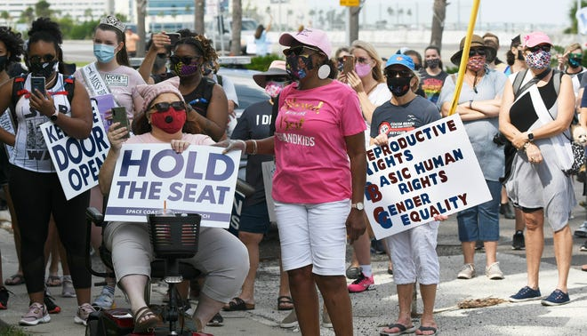 Participants in the Space Coast Women's March listen to speakers before their walk down SR520 in Cocoa Beach Saturday, Oct. 16, 2020. Craig Bailey/FLORIDA TODAY via USA TODAY NETWORK