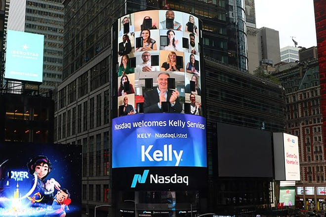 Kelly President/CEO Peter Quigley, center, is seen on the video board clapping after he rang the closing bell virtually Friday at the NASDAQ stock exchange.