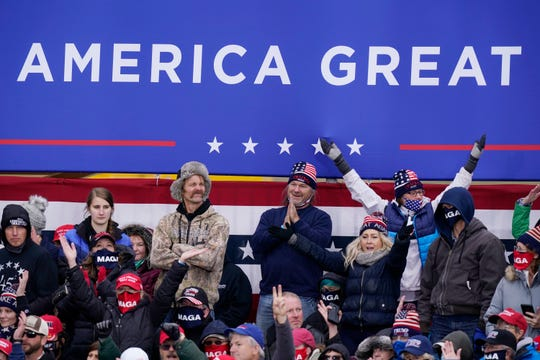 Supporters of President Donald Trump cheer as he speaks at an election rally on Saturday October 17, 2020, in Norton Shores.