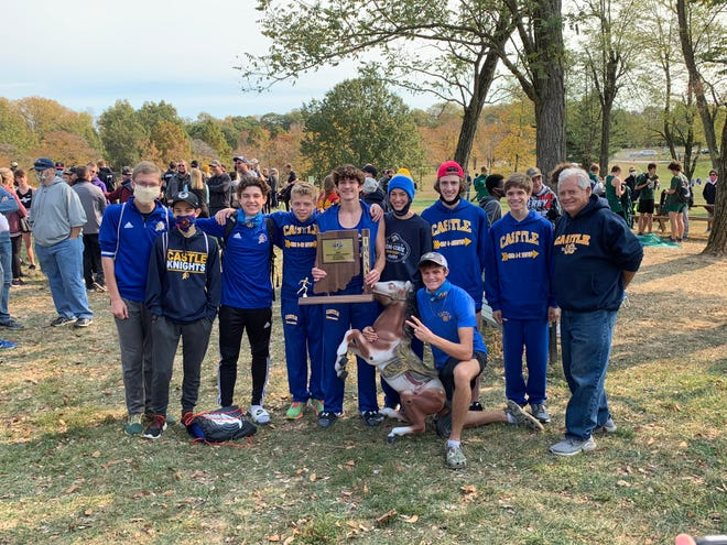 The Castle boys cross country team poses with the regional championship trophy.