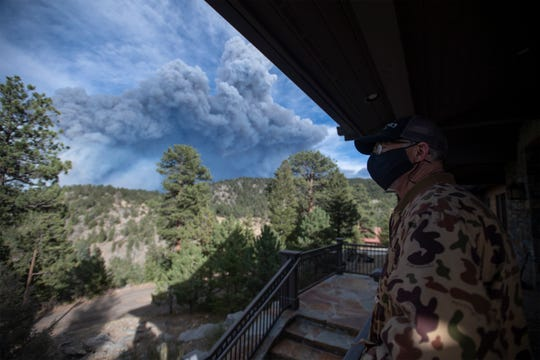 A resident looks out from his porch at the Cameron Peak Fire, the largest wildfire in Colorado history, as it burns outside Estes Park, Colo. on Friday, Oct. 16, 2020.
