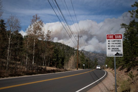 A sign informs motorists of a fire ban as smoke from the Cameron Peak Fire, the largest wildfire in Colorado history, drifts near Estes Park, Colo. on Friday, Oct. 16, 2020.