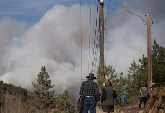 People watch as smoke from the Cameron Peak Fire fills the sky as the fire burns outside Estes Park, Colo. on Friday, Oct. 16, 2020.