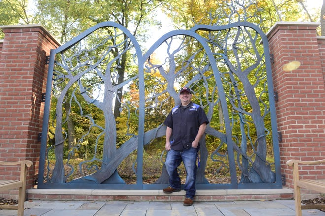 Ryan McKenna stands in front of the new gate he painted that stands at Kingwood Center Gardens.
