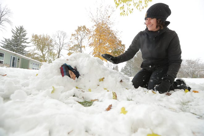 Cathy Bary buries her son Owen, 5, in the snow near their home in Fox Point along Santa Monica Blvd. near Lombardy Drive.