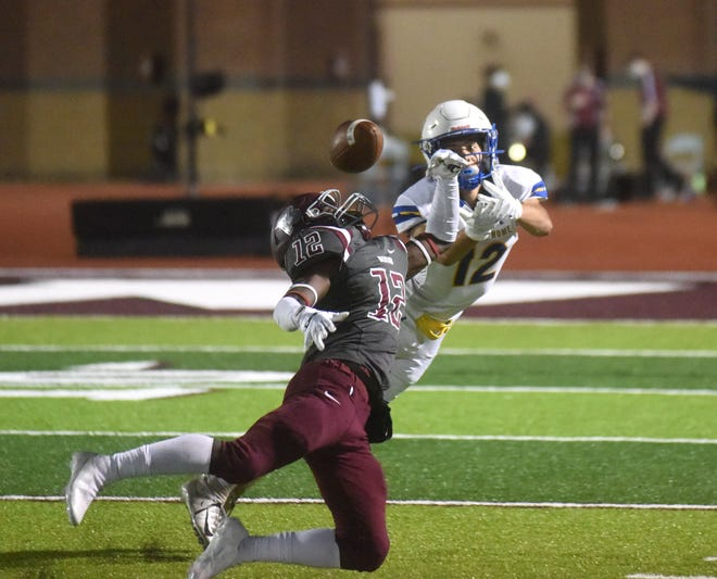 Mountain Home's Anthony Mojica battles Benton's Chris Bronson for a pass on Friday night at Benton.