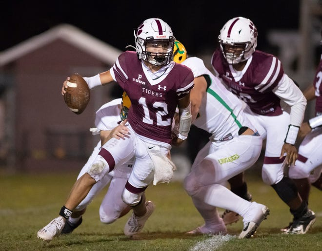 Quarteback Nate Simmons (12) tries to evade Crusader pressure during the Catholic vs PHS football game at Pensacola High School on Friday, Oct. 16, 2020.