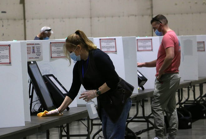 An election worker cleans a voting machine site at the Reno-Sparks Convention Center in Nevada on Saturday.