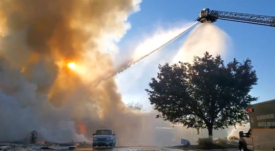 Firefighters battle flames at a shopping center early Saturday, Oct. 17, 2020 in Harrisonburg, Va.  Officials say an explosion and subsequent fire at the shopping center has injured a few people. (Ian Munro/Daily News-Record via AP)