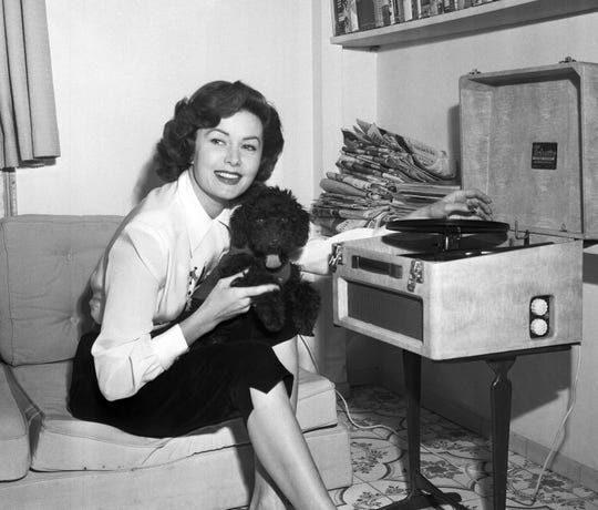 In this March 1, 1955 file photo, Actress Rhonda Fleming reads in her penthouse apartment in Rome.  Actress Rhonda Fleming, the fiery redhead who appeared with Burt Lancaster, Kirk Douglas, Charlton Heston, Ronald Reagan and other film stars of the 1940s and 1950s, has died, Wednesday, Oct. 14, 2020. She was 97.