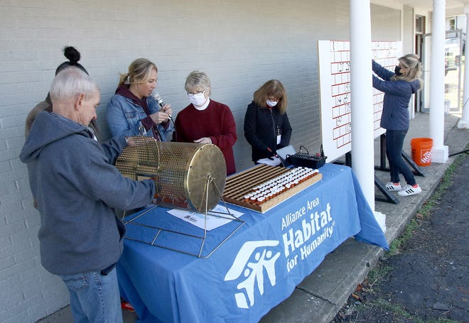 Alliance Area Habitat for Humanity board members pull names and numbers Saturday, Oct. 17, 2020, as part of a reverse raffle during the agency's drive-thru fundraiser held at Habitat's future headquarters on South Arch Avenue.