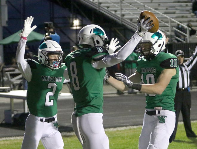 West Branch's Nicholas Wilson, left, and Josh Gregory, right, celebrate after Andrew Coffee (8) scores a first-quarter touchdown against East Liverpool during their second-round football playoff game at West Branch on Saturday, October 17, 2020.
