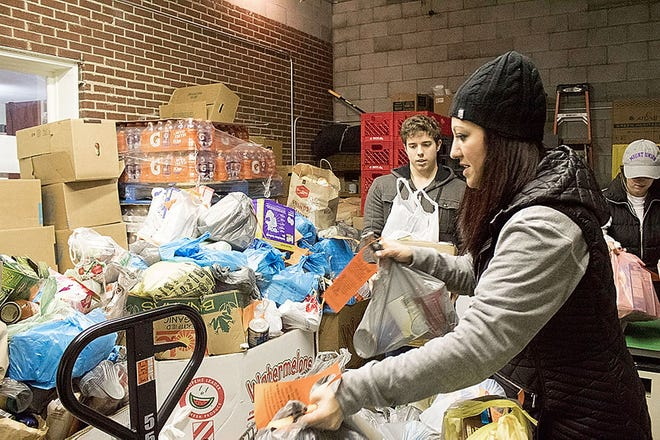 Abby Honaker Schroeder, director of Mount Union's Regula Center for Public Service, helps organize the more than 4,500 pounds of food donated in 2017 as part of the school's Trick-or-Treat for Canned Goods.
