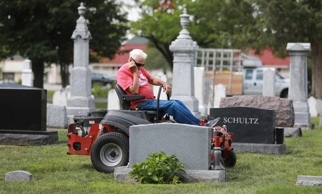 Bob Giehl, 95, pauses at the grave of his wife and son as he mows the grass at St. James Lutheran Church in September. Giehl, his son and a close family friend tend the church and cemetery to honor church members lost loved ones.