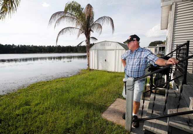 Stephen Booth stands on the back porch of his manufactured home in Kove Estates in Osteen on Friday, Oct. 16, 2020, where the waters of Little Lake have been nearing his home due to extensive rainfall.