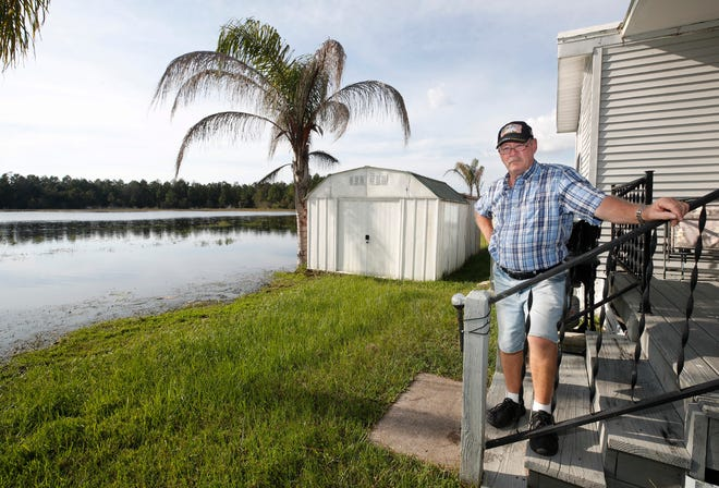 Stephen Booth stands on the back porch of his home in Osteen's Kove Estates where the waters from Little Lake encroach on his backyard, on Oct. 16, 2020. Several residents of the neighborhood, Booth included, are worried about the potential impact on the lake's water levels if a developer brings 189 homes to the region.