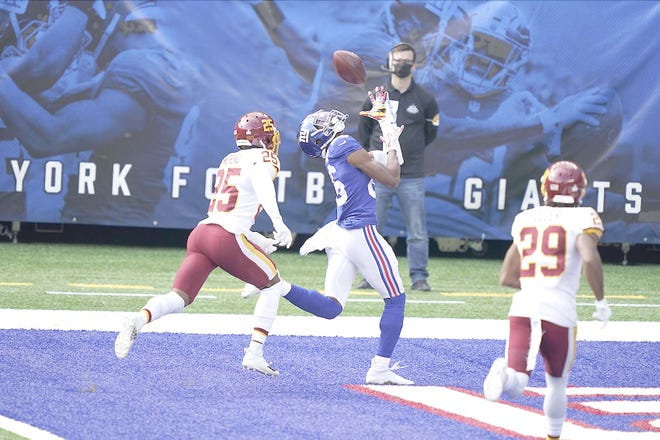 New York Giant Darius Slayton catches a pass for a touchdown in front of the Washington Football Team's Fabian Moreau (25) and Kendall Fuller (29) during the first half of Sunday's game in East Rutherford, New Jersey.