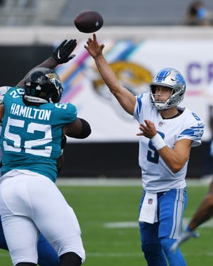Lions quarterback Matthew Stafford (9) throws a first-quarter pass as Jaguars defensive tackle DaVon Hamilton (52) attempts to rush. The Jaguars failed to sack Stafford during Sunday's game.