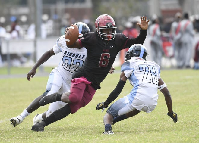 Raines quarterback Carleton Butler jr. (6) dodges Ribault defenders during the Northwest Classic in October.