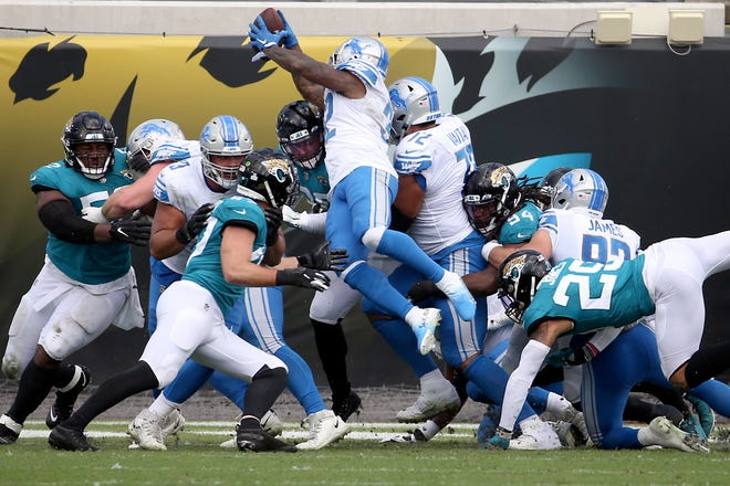 Detroit Lions running back D'Andre Swift, center, leaps over the line for a 1-yard touchdown against the Jacksonville Jaguars during the first half Sunday in Jacksonville.
