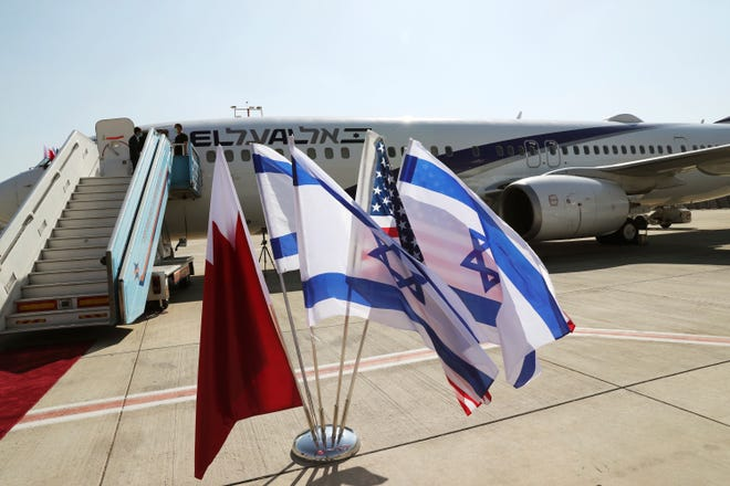 The national flags of Bahrain, Israel and America, flutter in near the Israeli flag carrier El Al plane that will fly an Israeli delegation, accompanied by U.S. aides, to Bahrain to formalise relations and broaden Gulf cooperation, at Ben Gurion airport in Lod, near Tel Aviv, Israel, on Sunday.