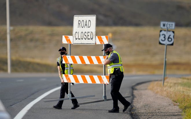 Police officers move a barricade at a roadblock on northbound Highway 36 at Broadway as nearby residents evacuate as a wildland fire races through the mountains late Saturday in Boulder, Colo.
