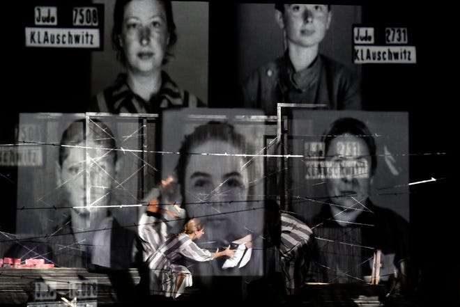 """Portraits of Auschwitz death camp prisoners are displayed on a mesh, as actresses of the Jewish State Theatre perform during the premiere of the """"The Beautiful Days of My Youth"""" play, based on the diary of Romanian Jewish Holocaust survivor Ana Novac, in Bucharest on Friday. Maia Morgenstern, head of the Jewish State Theater and a Romanian Jewish actress best known for playing Mary in Mel Gibson's controversial 2004 movie """"The Passion of the Christ,"""" described the play's staging in an interview with The Associated Press as an """"all-feminine project."""""""